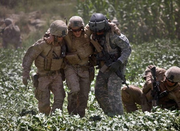 Marines help one of their wounded in Afghanistan in 2010. By Brennan Linsley/AP Images.